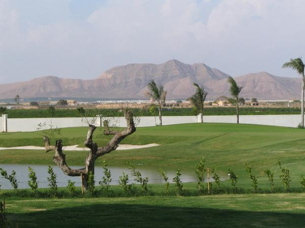 """The mountain is called """" big head """" Golf course with aquatic obstacle and sand bunker. Behind the limitation wall of the golf resorts is the mountain looking like a big head."""