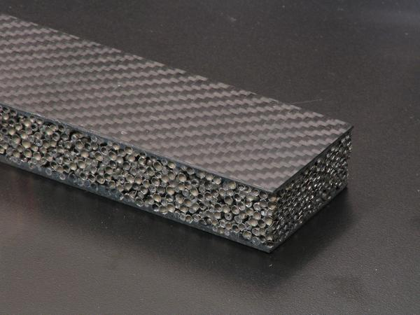 Carbon fibers with steel hollow balls The surface from carbon fibers, in between a kind of metal foam. Many small hollow balls from steel form a frothy structure. High firmness with light weight.