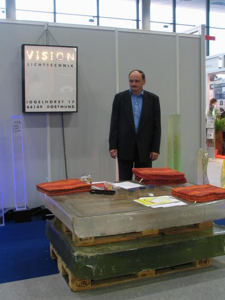 Tension arm molten glass 2 about 15 cm thick glass plates show in the exhibition stand of Vision light technology what they can do: Tension lack glass and thus create new formative possibilities.