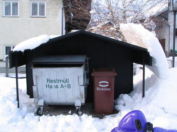 Snow turned over from the roof Over the garbage container is a tin roof. The sun was sining on the left side. The heat had spread out to the right side and melted a thin layer of snow.